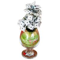 Денежное дерево 100 долларов89852Настольная композиция выполнена в виде миниатюрного денежного дерева. На пластиковое основание дерева насажены миниатюрные купюры-дубли достоинством в 100 долларов.Дерево закреплено в стеклянном бокале, оформленном искусственными листьями и различными декоративными элементами. На основании бокала расположена забавная божья коровка. Характеристики: Высота:23,5 см. Материал:стекло, пластик, бумага. Производитель:Россия. Артикул:89852