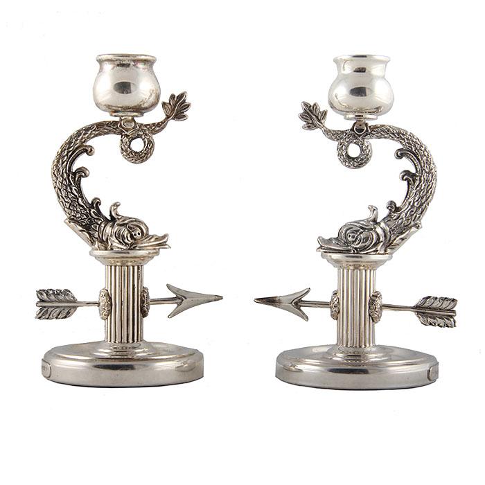"""Подсвечники парные """"Рыбы"""". Белый металл. House of Faberge, вторая половина ХХ века.                              Высота 15 см, ширина 9,5 см.                 Сохранность хорошая. На основаниях клейма  """"Faberge"""".     Основания подсвечников выполнены в виде колонн, пронзенных стрелами. На них расположены изогнутые фигуры рыб, на хвостах которых находятся изящные округлые чаши для свеч.     Очень необычная идея оформления этих предметов позволит им стать ярким украшением интерьера.      Все детали подсвечников тщательно проработаны, глубокий рельеф прекрасно демонстрирует объем элементов, тонко  обработаны   чешуя, завитки на спинах рыб, перья на стреле.    Все это составляет высокий класс изделия, дороговизну и  богатство отделки."""