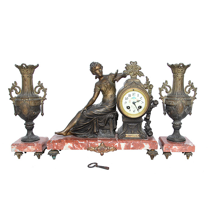 """Идеально для роскошного представительского подарка высокопоставленному лицу! Часы и касолеты """"Кокетка"""". Бронза, роспись, латунь, мрамор, эмаль. Франция, около 1880-го года.Размеры часов: высота 34 см, длина 38 см, глубина 15 см. Диаметр циферблата 8 см. Касолеты: высота 34 см, размер основания 11 х 11 см.Сохранность очень хорошая. Незначительный дефект литья на одной из касолет. На механизме клеймо """"Societe Clusienne S.C.A.P.H. Cluses"""" и индивидуальный номер 23821. Под часами шильда """"COQUETTERIE par Ruffony"""" (""""КОКЕТКА скульптора Руффони"""").На циферблате надписи на французском языке  (неразборчиво, частично стерты). Оригинальные маятник и ключ - в комплекте. Часы приятно бьют каждые полчаса и каждый час. Композиция создана скульптором О. Руффони (O. Ruffony) - известным итальянским мастером конца XIX-го-начала XX вв. Роскошные часы украшены фигурным изображением юной девушки, которая, гордая своей красотой и знающая ей цену, кокетливо смотрит на свое отражение в зеркале и улыбается. Изумительно проработаны все детали композиции. Легкая, миниатюрная фигурка отличается замечательной грацией и изяществом. Классический гарнитур дополнен двумя парными касолетами в виде античных амфор. Обилие декора придает предметам особенную торжественность и парадный вид. Не пропустите поистине раритетный экземпляр часов, дополненных парой великолепных касолет! Обращаем ваше внимание, что  для идеального хода любые механические часы после приобретения и транспортировки нуждаются в настройке у часового мастера."""