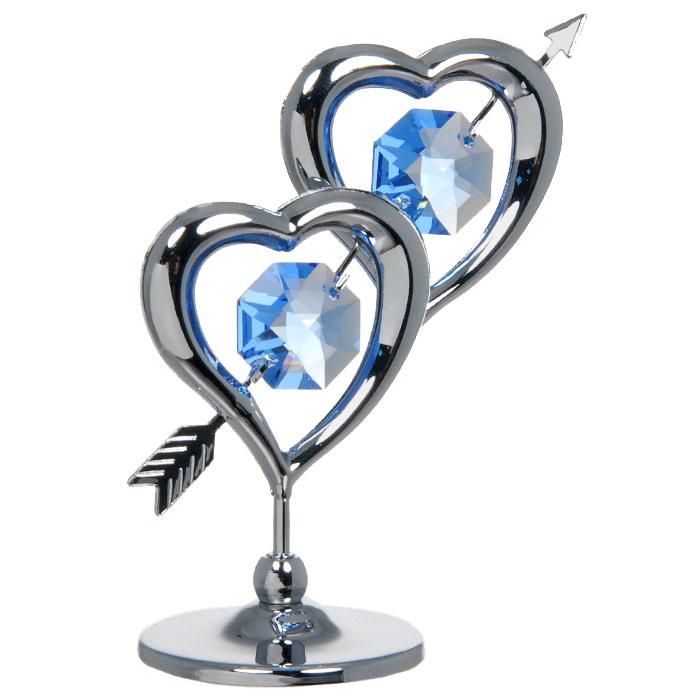 """Декоративное изделие в виде двух сердец пронзенных одной стрелой, украшенных посередине голубыми кристаллами Swarovski, изготовлено из высококачественной стали. Оригинальная миниатюра будет отличным подарком для ваших друзей и коллег.  Более 30 лет компания """"Crystocraft"""" создает качественные, красивые и изящные сувениры, декорированные различными кристаллами Swarovski.  Характеристики:  Материал:  сталь, кристаллы Swarovski.  Высота:  6,5 см. Размер коробки:  7 см х 9 см х 4,5 см. Артикул:  U0236-001-CBL. Производитель: Китай."""