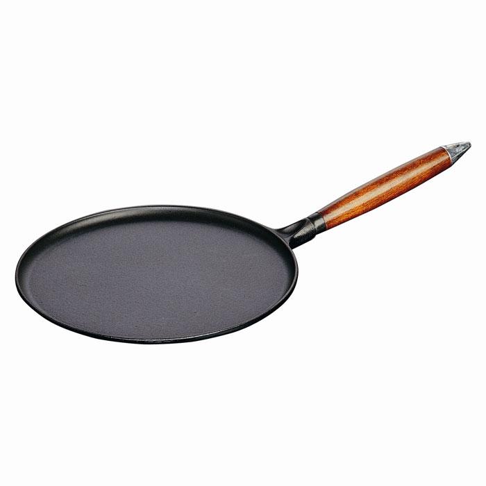 """Сковорода """"Staub"""" изготовлена из чугуна и покрыта эмалью снаружи и внутри. Она имеет очень низкие бортики, что делает ее удобной для приготовления блинов и оладьев. Особая форма бортиков позволяет легко перевернуть блюдо и облегчает сервировку. Высокая теплоемкость чугуна позволяет ему сильно нагреваться и медленно остывать, а это в свою очередь обеспечивает равномерное приготовление продуктов. Пища, приготовленная в чугунной посуде, сохраняет свои вкусовые качества, и благодаря экологической чистоте материала, не может нанести вред здоровью человека. Также чугунная сковорода обладает высокой прочностью и износоустойчивостью.  Сковорода оснащена удобной деревянной ручкой, которая дает возможность забыть о прихватках, но и накладывает ограничения на использование посуды в духовке. Также в комплект входят деревянная лопатка и приспособление для распределения теста по поверхности сковороды. Сковорода """"Staub"""" подходит для использования на всех типах кухонных плит.   Характеристики:  Материал:  чугун, дерево. Диаметр сковороды:  28 см. Высота стенки сковороды:  1 см. Длина ручки:  24 см. Длина лопатки:  27,5 см. Размер приспособления для распределения теста:  14 см х 14 см. Размер упаковки:  52 см х 7,5 см х 29 см. Производитель:  Франция. Артикул:  1212823.  Торговая марка """"Staub"""" разрабатывает и создает высококлассные предметы кухонной утвари, которые совмещают традиции и современность, умения наших предков и передовые технологии. Продукция """"Staub"""" - прекрасное сочетание красоты и функциональности. Она подходит как искусным поварам, так и любознательным дебютантам, готовым познавать удовольствие от вкусной и здоровой пищи. Философия создателя марки Франциса Стоба заключается в том, что каждая деталь - уникальна. Чтобы гарантировать вам постоянное оптимальное функционирование и возможность раскрыть вкусовые качества ваших продуктов, вся продукция """"Staub"""" проходит самые строгие испытания. Однако, каждое изделие имеет свои особенности и нюансы, поскольку отливается в инди"""