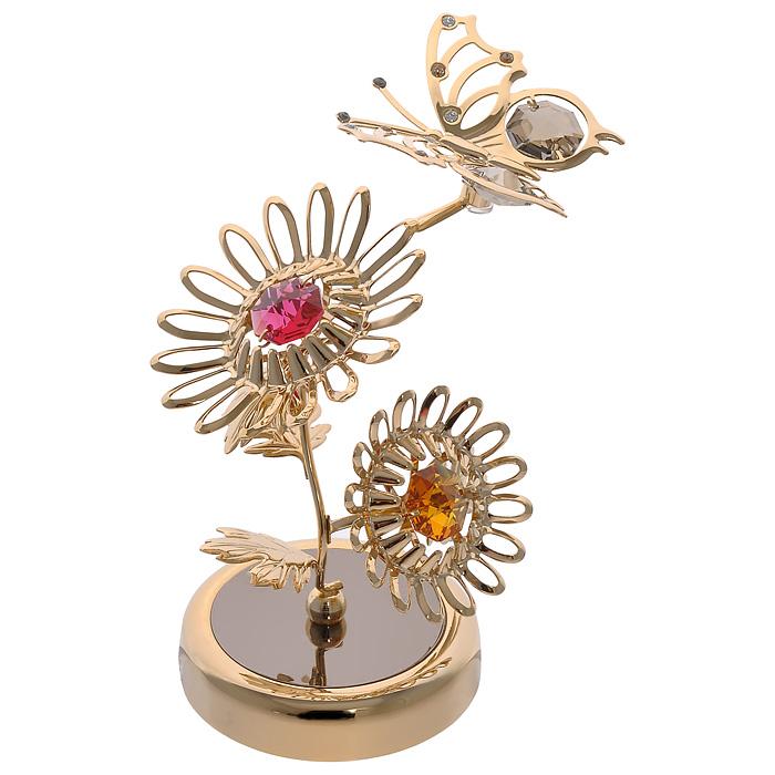Фигурка декоративная Бабочка на цветах, цвет: золотистый. 6729567295Декоративная фигурка Бабочка на цветах, золотистого цвета, станет необычным аксессуаром для вашего интерьера и создаст незабываемую атмосферу. Фигурка выполнена в виде двух цветков и бабочки, расположенных на подставке, и инкрустирована разноцветными кристаллами. Кристаллы, украшающие фигурку, носят громкое имяSwarovski. Ограненные, как бриллианты, кристаллы блистают сотнями тысяч различных оттенков. Эта очаровательная вещь послужит отличным подарком близкому человеку, родственнику или другу, а также подарит приятные мгновения и окунет вас в лучшие воспоминания. Фигурка упакована в подарочную коробку. Характеристики:Материал: металл (углеродистая сталь, покрытие золотом 0,05 микрон), австрийские кристаллы. Размер фигурки: 8,5 см х 10,5 см х 6 см. Размер упаковки: 8,5 см х 13 см х 8,5Артикул: 67295. Более чем 30 лет назад компанияCrystocraftвыросла из ведущего производителя в перспективную торговую марку, которая задает тенденцию благодаря безупречному чувству красоты и стиля.Компания создает изящные, качественные, яркие сувениры, декорированные кристалламиSwarovskiразличных размеров и оттенков, сочетающие в себе превосходное мастерство обработки металлов и самое высокое качество кристаллов.Каждое изделие оформлено в индивидуальной подарочной упаковке, что придает ему завершенный и презентабельный вид.