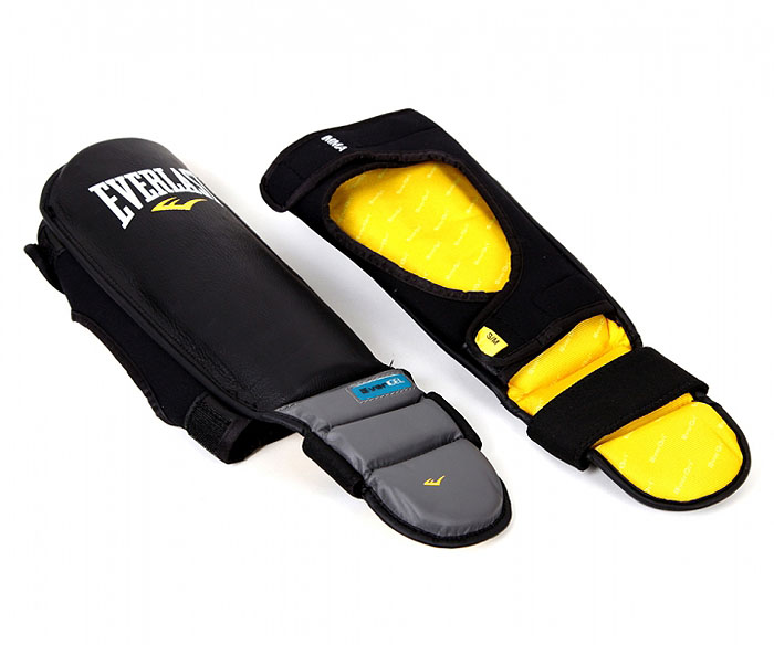 """Защита голени Everlast """"ММА"""" предназначена для предотвращения травм от ударов во время занятий спортом, тренировок и единоборств.  Верхняя поверхность защиты выполнена из натуральной кожи, внутренняя - из пены. Технология Evergel обеспечивает амортизацию и защиту суставов. Защита крепится к голени при помощи двух широких ремней на липучках. Характеристики:  Размер: L/XL. Размер защиты: 50 см х 16 см. Материал:  кожа, текстиль, пена. Артикул:  7950LXLGLU. Размер упаковки:  35 см х 17 см х 11 см."""