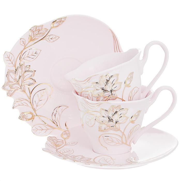 Набор чайный Розовая лиана, 4 предмета595-114Чайный набор Розовая лиана, выполненный из высококачественного фарфора розового цвета, состоит из двух чашек и двух блюдец. Изделия декорированы рельефным цветком, покрытым золотистой эмалью. Элегантный дизайн и совершенные формы предметов набора привлекут к себе внимание и украсят интерьер вашей кухни. Чайный набор Розовая лиана идеально подойдет для сервировки стола и станет отличным подарком к любому празднику.Чайный набор упакован в подарочную коробку из плотного картона золотистого цвета. Внутренняя часть коробки задрапирована белой атласной тканью, и каждый предмет надежно крепится в определенном положении благодаря особым выемкам в коробке. Характеристики:Материал:фарфор. Объем чашки:200 мл. Диаметр чашки по верхнему краю: 9 см. Высота чашки: 7 см. Диаметр блюдца: 15 см. Размер упаковки: 23 см х 18 см х 11 см. Артикул: 595-114.