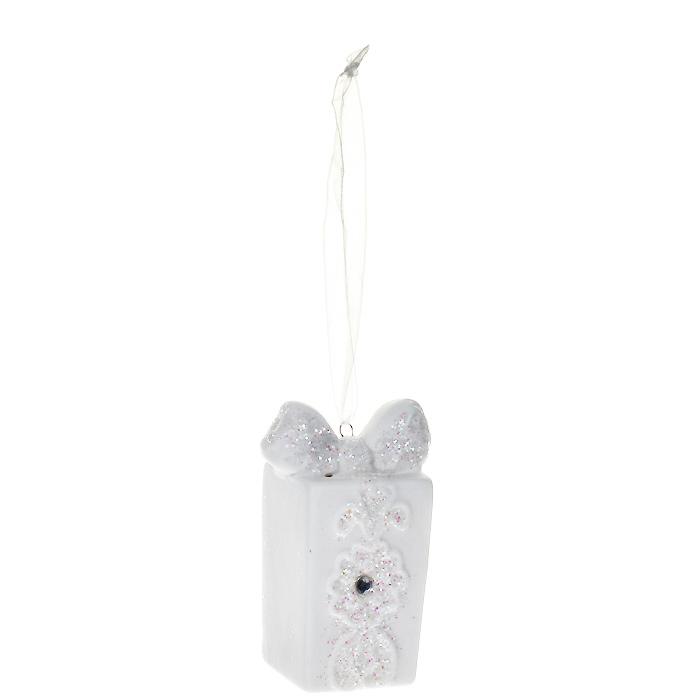 Новогоднее подвесное украшение Подарок, цвет: белый. 2593325933Оригинальное новогоднее украшение выполнено из керамики в виде подарка, оформленного блестками и стразом. С помощью специальной петельки украшение можно повесить в любом понравившемся вам месте. Но, конечно, удачнее всего такая игрушка будет смотреться на праздничной елке.Новогодние украшения приносят в дом волшебство и ощущение праздника. Создайте в своем доме атмосферу веселья и радости, украшая всей семьей новогоднюю елку нарядными игрушками, которые будут из года в год накапливать теплоту воспоминаний. Коллекция декоративных украшений из серии Magic Time принесет в ваш дом ни с чем несравнимое ощущение волшебства! Характеристики:Материал: керамика, стразы, текстиль, блестки. Цвет: белый. Размер украшения: 4 см х 3 см х 7 см. Артикул: 25933.