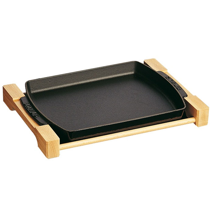 Форма для выпечки Staub на деревянной подставке, 33 см х 23 см, цвет: черный. 12052231205223Прямоугольная форма для выпечки Staub изготовлена из высококачественного чугуна, покрытого эмалью снаружи и внутри. Чугунная форма идеально подойдет для запекания мяса, рыбы и птицы как в духовке, так и на открытом огне. Деревянная подставка позволит подавать приготовленные блюда с плиты прямо на стол, а на природе станет незаменимым аксессуаром, который не позволит испачкать форму или прожечь полиэтиленовую скатерть. Простая в уходе и долговечная в использовании форма будет верной помощницей в создании ваших кулинарных шедевров. Эмалевое покрытие Staub не окисляется при приготовлении пищи.Подходит для использования на всех типах плит и в духовке. Пригодна для мытья в посудомоечной машине. Характеристики: Материал: чугун. Размер формы с подставкой: 33 см х 23 см х 4 см. Размер формы с ручками (без подставки): 29 см х 21 см х 2,5 см. Размер упаковки: 35 см х 24 см х 4,5 см. Производитель: Франция. Артикул: 1205223.