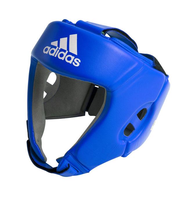 """Боксерский шлем Adidas """"AIBA"""" разработан и спроектирован для обеспечения максимальной защиты и  оптимальной видимости. Шлем сертифицирован Международной ассоциацией бокса (AIBA). Оболочка  шлема изготовлена из натуральной кожи, что увеличивает срок эксплуатации шлема. Внутреннее наполнение из  пены, изготовленной по технологии Air Cushion, обеспечивает отличную амортизацию ударных нагрузок.  Внутренняя подкладка выполнена из высокотехнологичной, искусственной кожи Amara. Шлем имеет легкую  конструкцию без защиты скул. Два широких ремня фиксируемых липучкой на теменной части и два ремня на  липучке в затылочной части позволяют регулировать размер шлема и обеспечивают плотную и удобную посадку,  исключая смещение шлема во время боя. Так же шлем имеет регулируемый ремешок под подбородком."""