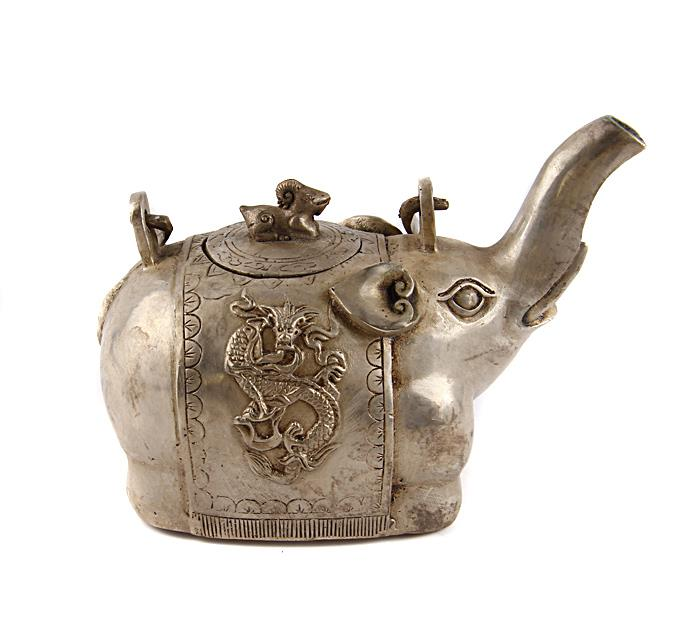 """Чайник """"Дракон"""" в традиционном восточном стиле. Металл, прочеканка. Китай, середина XX века. Высота 11 см, длина 15 см, ширина 9 см. На дне иероглифическое клеймо. Сохранность хорошая. На Востоке особое значение имеют форма и цвет чайников и чайных сервизов. Чайник выполнен в виде величественного слона, поднявшего хобот в знак приветствия.Оригинальный чайник в китайском стиле станет прекрасным подарком любителям Востока и ярким элементом декора. Прекрасный образец декоративно-прикладного искусства Китая!"""