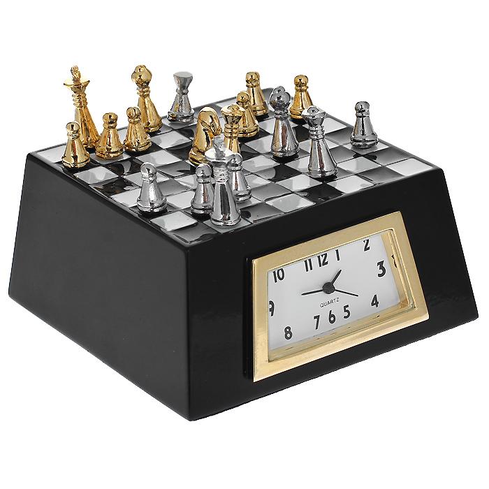 """Настольные кварцевые часы """"Шахматы"""" изготовлены из сплава цинка, покрытого   лаком черного цвета. Часы выполнены в виде шахматной доски с фигурами. Сбоку   расположен циферблат белого цвета в форме трапеции. Тип индикации - арабские   цифры. Часы имеют три стрелки - часовую, минутную и секундную. Дно отделано   бархатистой тканью для предотвращения скольжения.  Изящные часы красиво оформят стол дома или в офисе и станут приятным   сувениром любителю шахмат.   Характеристики:  Материал: сплав цинка. Размер часов (ДхШхВ): 6,3 см х 6,3 см х 4,5 см. Цвет: черный. Размер циферблата: 3,2 см х 1,5 см."""