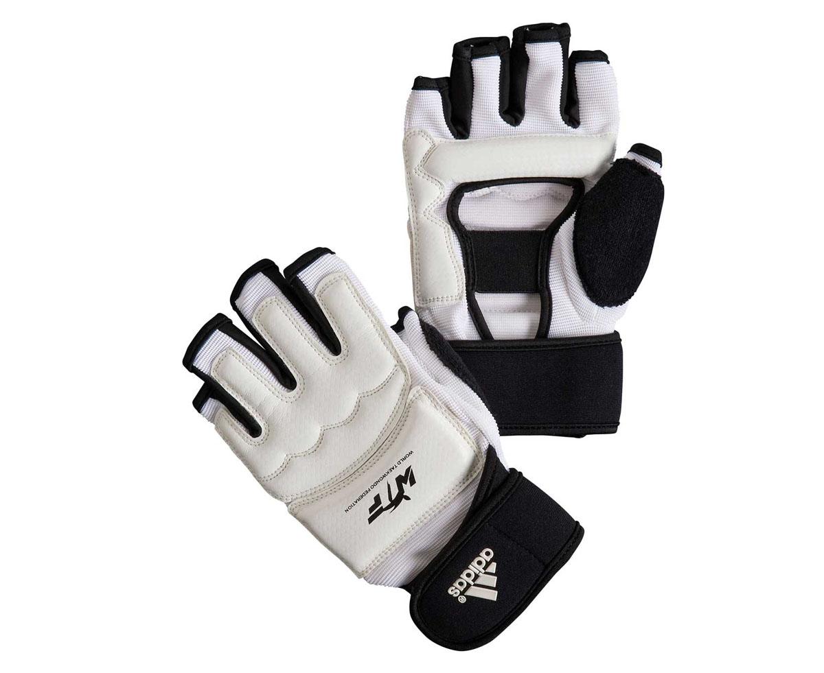 Перчатки для тхэквондо Adidas Fighter Gloves WTF, цвет: белый. Размер S691601Боевые перчатки Adidas Fighter Gloves предназначены для занятий тхэквондо и другими видами единоборств. Они отлично защищают суставы рук, но при этом не сковывают движения. В отличие от боксерских перчаток, они имеют обрезанные пальцы и открытую ладонь, что позволяет осуществлять захват. Перчатки Adidas Fighter Gloves WTF выполнены из искусственной кожи. Они обладают повышенной устойчивостью к изнашиванию. Перчатки прочно фиксируются на запястье широкой манжетой на липучке, что гарантирует быстроту и удобство одевания.