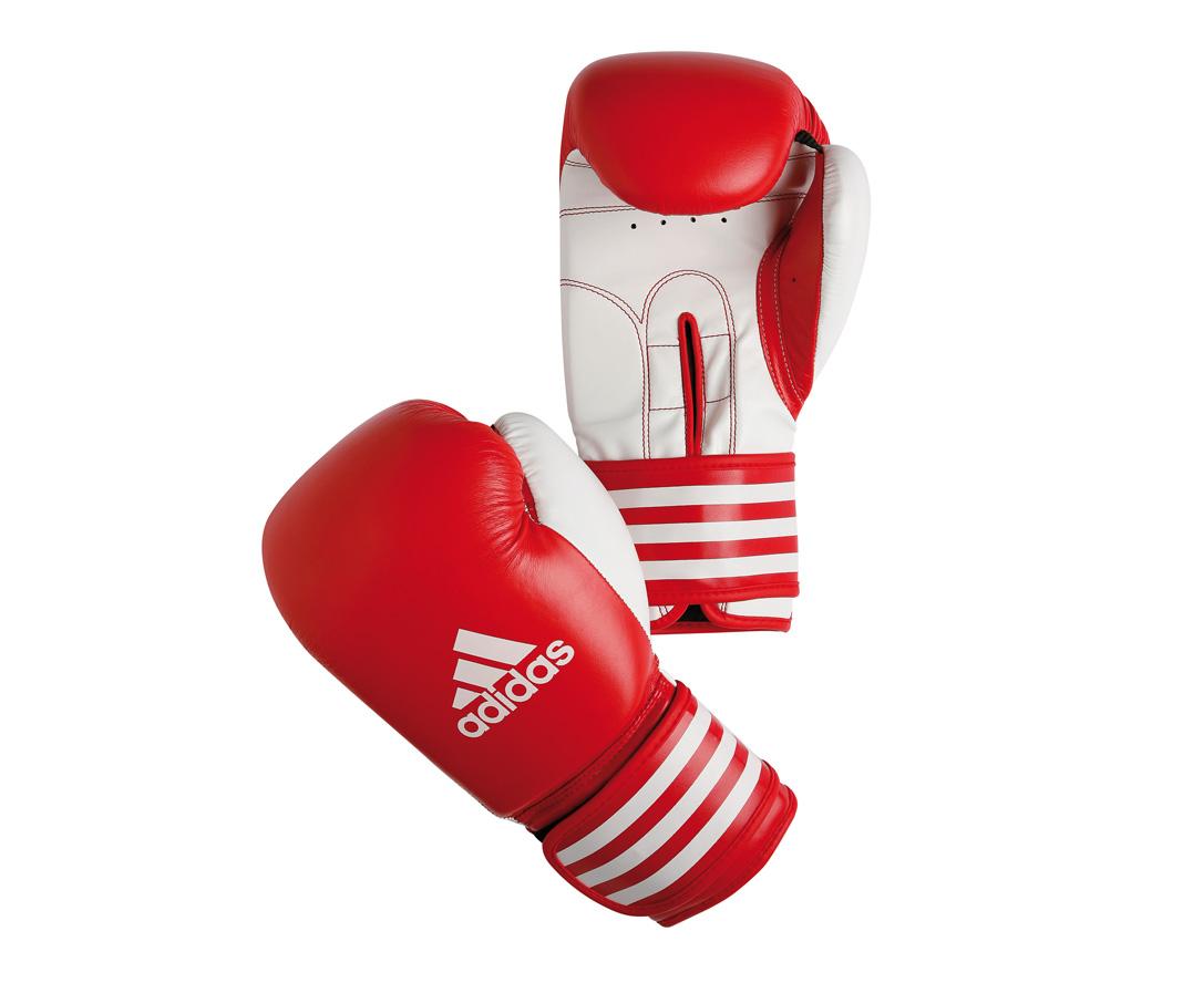 Перчатки боксерские Adidas Ultima Competition, цвет: красно-белый. adiBC02. Вес 10 унцийadiBC02Боксерские перчатки Adidas Ultima Competition для отработок ударов и комбинаций. Тыльная сторона в перчатках выполнена из прочной, износостойкой, натуральной кожи. Внутренний наполнитель, выполненный из формованной под давлением пены с интегрированной внутренней вставкой из геля, выполненной по технологии I-Protech, покрывает тыльную сторону, создавая надежную защиту рук и давая боксеру возможность безопасно тренироваться в полную силу. Внутренняя подкладка, выполненная из дышащего материала, и вентиляционное отверстие на ладони создают комфортный микроклимат внутри перчаток. Эластичный ремешок с фиксацией на липучке позволяет быстро одеть и снять перчатки.