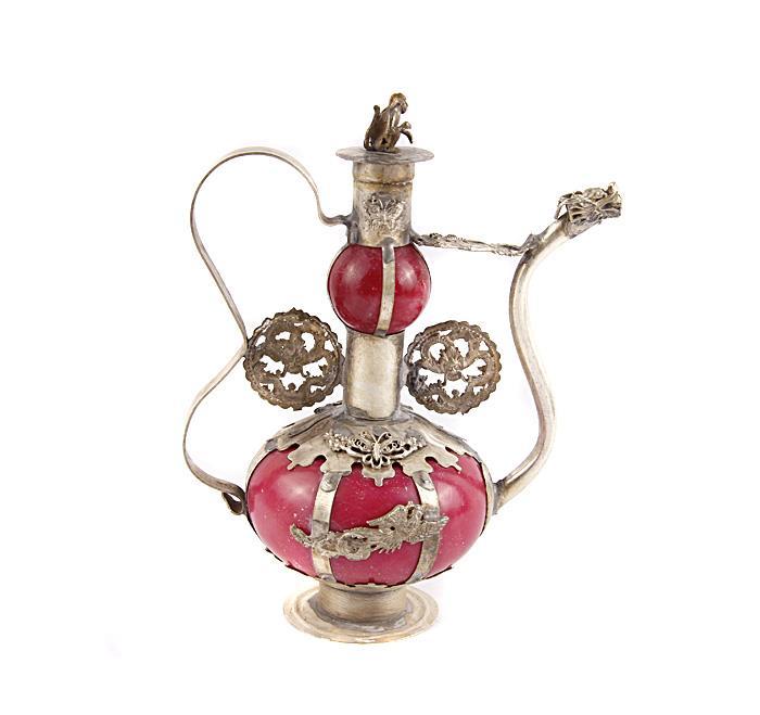 Традиционный тибетский чайник. Металл, прочеканка, искусственный камень. Китай, вторая половина XX века. Высота 15 см, длина 11,5 см, ширина 7 см. Сохранность хорошая.  На Востоке особое значение имеют форма и цвет чайников и чайных сервизов. В оформлении этого изящного чайника сочетается яркое колористическое решение (основа из искусственного камня) и необычный металлический декор. Оригинальный чайник в тибетском стиле станет прекрасным подарком любителям Востока и ярким элементом декора. Прекрасный образец декоративно-прикладного искусства Тибета, оригинальный подарок почитателю буддийской культуры.