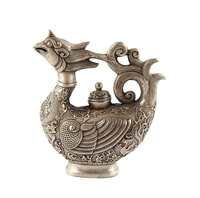 """Чайник """"Чудо-птица"""" в тибетском стиле. Металл, прочеканка. Китай, вторая половина XX века. Высота 19 см, длина 17 см, ширина 7 см. На дне иероглифическое клеймо. Сохранность хорошая. На Востоке особое значение имеют форма и цвет чайников и чайных сервизов. Оригинальный фигурный чайник из сплава серебристого цвета выполнен в виде прекрасной диковинной птицы. Оригинальный чайник в тибетском стиле станет прекрасным подарком любителям Востока и ярким элементом декора. Прекрасный образец декоративно-прикладного искусства Тибета, оригинальный подарок почитателю буддийской культуры."""