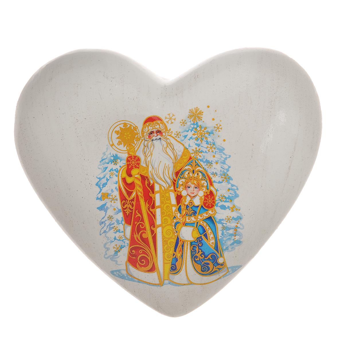 """Декоративное украшение """"Новогоднее сердце"""" поможет украсить дом к праздникам. Фигурка выполнена из керамики в форме сердца и оформлена изображением деда Мороза и Снегурочки. Вы можете поставить украшение в любом месте, где оно будет удачно смотреться, и радовать глаз. Так же фигурку можно повесить на стену с помощью специального отверстия. Такое украшение станет великолепным новогодним сувениром."""