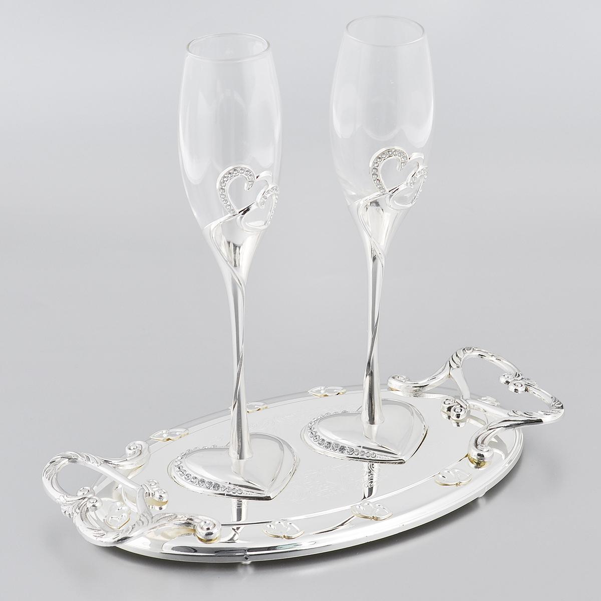 """Набор Marquis """"Свадьба"""" состоит из двух бокалов для шампанского для  молодоженов и подноса. Бокалы выполнены из стекла. Изящные тонкие ножки,  выполненные из стали с серебряно-никелевым покрытием, оформлены  перфорацией в виде двух сплетенных сердец, инкрустированных стразами.  Основание в виде сердца также оформлено стразами.  Овальная подставка с ручками, украшенная гравировкой и рельефом, прекрасно  дополняет набор.  Такой набор принесет особую атмосферу торжества и праздника."""