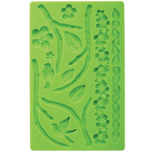 Молд для нанесения рисунка на мастику Wilton Природа, цвет: зеленый, 20 см х 12,5 смWLT-409-2Молд для нанесения рисунка на мастику Wilton Природа, выполненный из силикона, поможет вам легко нанести рисунки на мастику и сахарную пасту для тортов и сладких угощений. Молд содержит формы в виде цветов, веток и листьев.Использование и хранение: Перед первым использованием и после каждого применения вымойте молд в мыльной воде или на верхней полке в посудомоечной машине. Хорошо высушите молд перед использованием.Полезные советы по использованию:- Для того, чтобы мастика или цветочная паста не прилипали к молду, посыпьте его сахарной пудрой или смажьте растительным жиром сахарную мастику прежде чем накладывать на нее молд,- При раскатывании сахарной мастики используйте скалку для того, чтобы вся мастика была в полостях молда,- Следуйте инструкциям по изготовлению украшений, разместите их на торте, высушите.Изготовление: Скатайте сахарную мастику в трубочку такого же размера, как и полость молда. Положите мастику в полость молда. Прижмите.Разрезание: Положите руку на мастику. Маленькой лопаткой обрежьте излишки мастики. Снимаем мастику: Переверните молд. Выньте сахарную мастику с получившимся рисунком.