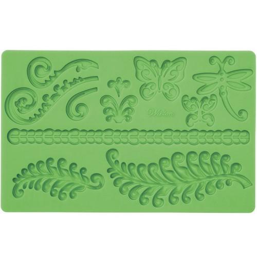 Молд для нанесения рисунка на мастику Wilton Папоротник и завитки, цвет: зеленый, 20 х 12,5 смWLT-409-2548Молд для нанесения рисунка на мастику Wilton Папоротник и завитки, выполненный из силикона, поможет вам легко нанести рисунки на мастику и сахарную пасту для тортов и сладких угощений. Молд содержит формы в виде бабочек, стрекоз и листьев папоротника.Использование и хранение: Перед первым использованием и после каждого применения вымойте молд в мыльной воде или на верхней полке в посудомоечной машине. Хорошо высушите молд перед использованием.Полезные советы по использованию:- Для того, чтобы мастика или цветочная паста не прилипали к молду, посыпьте его сахарной пудрой или смажьте растительным жиром сахарную мастику прежде чем накладывать на нее молд,- При раскатывании сахарной мастики используйте скалку для того, чтобы вся мастика была в полостях молда,- Следуйте инструкциям по изготовлению украшений, разместите их на торте, высушите.Изготовление: Скатайте сахарную мастику в трубочку такого же размера, как и полость молда. Положите мастику в полость молда. Прижмите.Разрезание: Положите руку на мастику. Маленькой лопаткой обрежьте излишки мастики. Снимаем мастику: Переверните молд. Выньте сахарную мастику с получившимся рисунком.