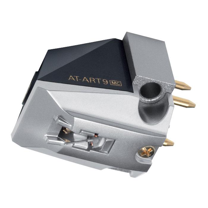 Audio-Technica AT-ART9 головка звукоснимателя15117956Головка звукоснимателя Audio-Technica AT-ART9 с подвижной катушкой с магнитным сердечником обладает выходным напряжением в 0,5 мВ и повторяет дизайн и некоторые конструктивные особенности культового юбилейного MC-картриджа Audio-Technica AT50ANV.Корпус модели имеет оригинальный внешний вид с характерными «рублеными» формами. Его основание изготовлено из прошедшего специальную машинную обработку алюминия и служит для крепления преобразователя – подвижной системы, состоящей из двух катушек с магнитными сердечниками, а также мощного неодимового магнита, позволяющего снизить массу и размеры картриджа. Верхняя часть корпуса выполнена из прочного пластика. Благодаря такой конструкции головке звукоснимателя удается уверенно противостоять паразитным резонансам.Провода катушек выполнены из бескислородной очищенной монокристаллической меди PCOCC, позволяющей обеспечить более качественную передачу сигнала. В преобразователе также задействованы элементы из пермендюра (сплав железа с кобальтом и ванадием), сосредоточенные вокруг основного неодимового магнита и служащие для усиления магнитного поля. Благодаря такой конструкции увеличивается выходное напряжение, обеспечивается высокая точность АЧХ и повышается качество звучания в СЧ/НЧ-диапазоне.Картридж AT-ART9 оснащен алмазной иглой со специальной заточкой Line Contact (40 мкм х 7 мкм), позволяющей точно считывать информацию с дорожки винилового диска. Консоль иглодержателя изготовлена из бора и имеет диаметр в 0,26 мм. Преимуществами данной модели является широкий частотный диапазон, находящийся в пределах от 15 до 50000 Гц, и достаточно высокий показатель разделения каналов (30 дБ). Вес картриджа составляет 8,5 грамм. Отличным вариантом для работы с данной головкой звукоснимателя станет повышающий трансформатор или же MC-фонокорректор с нагрузкой по входу, превышающей показатель в 100 Ом.Головка звукоснимателя AT-ART9 демонстрирует стабильные характеристики и способна обеспе
