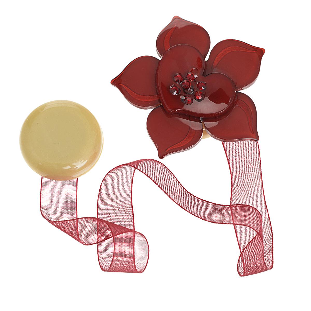 """Клипса-магнит """"Calamita Fiore"""", изготовленная из пластика и текстиля, предназначена для придания формы шторам. Изделие представляет собой два магнита, расположенные на разных концах текстильной ленты. Один из магнитов оформлен декоративным цветком и украшен стразами. С помощью такой магнитной клипсы можно зафиксировать портьеры, придать им требуемое положение, сделать складки симметричными или приблизить портьеры, скрепить их.   Клипсы для штор являются универсальным изделием, которое превосходно подойдет как для штор в детской комнате, так и для штор в гостиной. Следует отметить, что клипсы для штор выполняют не только практическую функцию, но также являются одной из основных деталей декора этого изделия, которая придает шторам восхитительный, стильный внешний вид. Материал: пластик, полиэстер, магнит. Диаметр декоративного цветка: 5 см. Диаметр магнита: 2,5 см. Длина ленты: 28 см."""
