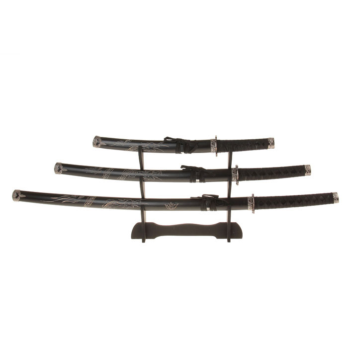 Сувенирное оружие Sima-land Катана, на подставке, цвет: черный, 3 шт. 272054272054Сувенирные мечи-катаны изготовлены из металла и выглядят очень реалистично. Рукоятки выполнены из пластика и декорированы черной лентой. Ножны выполнены из дерева и украшены резным драконом. Клинки не заточены. В комплекте деревянная подставка. Сувенирное оружие - это всегда блестящий подарок для мужчины, прекрасный вариант как для партнера по бизнесу, так и для любимого. Если вы заядлый коллекционер, то добавление нового декоративного оружия к своей коллекции будет ярким и приятным моментом в вашей жизни.Сувенирное оружие - это не просто подарок, но и гарантия хорошего настроения, ведь это красивая вещь из качественного, безопасного для здоровья материала.Длина катан (с ножнами): 100 см, 79 см, 54 см. Длина лезвий: 61,2 см, 43 см, 27 см.