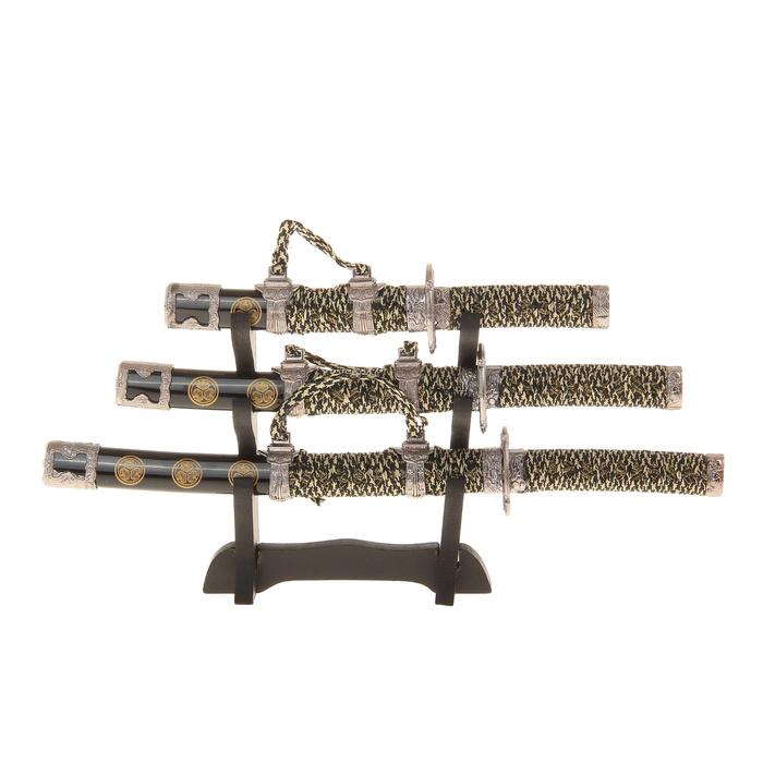 Сувенирное оружие Sima-land Катана, на подставке, 3 шт. 543291543291Сувенирное оружие Sima-land Катана - изысканный подарок для любителей восточных боевых искусств и коллекционеров. В набор входят три катаны разной длины в миниатюре, а также специальная подставка. Для каждой сабли предусмотрены пластиковые с ножны с красивым орнаментом в восточном стиле. Тати - самый большой меч придворных самураев, имеет большую, чем у катаны, длину клинка и изогнутость. Это связано с тем, что знатные самураи воевали на лошадях, и увеличенная длина была нужна, чтобы доставать до пригнувшихся противников, а большая изогнутость - для нанесения рубящих ударов. Вакидзаси (короткий меч), парный меч к катане, самурай носил с собой всегда, это было средство самообороны в те времена. И средний меч, дайто, самурай всегда носил с собой, даже в гости - это было его лицо, и о том, как выглядел внешне меч, можно было многое рассказать о хозяине. Клинок мечей выполнен из высококачественного металла (не заточен). Ножны и рукоятка декорированы пластиковыми элементами серебристого цвета с изысканным рельефом, тесьмой с золотистым люрексом и оплеткой, как у настоящего оружия. Катаны выполнены с невероятной точностью и достоверностью. Внимание к мельчайшим деталям делает эти реплики очень реалистичными. По мнению коллекционеров всего мира, катана - самое совершенное оружие. С одной стороны, оно смертоносное, а с другой - воплощение утонченности и элегантности. Геометрия этого оружия поражает своей простотой и лаконичностью. Сувенирное оружие на подставке станет изысканным подарком и прекрасным дополнением интерьера вашей квартиры или офиса. Длина катан: 21 см; 27 см; 33 см.