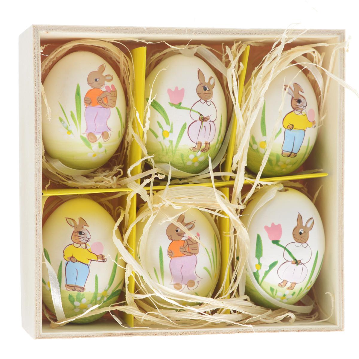 """Декоративные подвесные пасхальные яйца """"Феникс-презент"""" отлично подойдут  для декорации вашего дома к Пасхе. Изделия выполнены из натуральной скорлупы  куриного яйца и декорированы изображением кроликов и цветов. Украшения оснащены  специальными текстильными петельками для подвешивания. В комплекте - 6  пасхальных яиц, которые располагаются в деревянном ящике с подложкой из  лыко.  Яйцо - это главный символ Пасхи, который означает для христиан новую жизнь и  возрождение. Создайте в своем доме атмосферу праздника, украшая его  декоративными пасхальными яйцами.  Материал: скорлупа куриного яйца, текстиль, лыко. Размер яйца: 4 см х 4 см х 5,5 см."""
