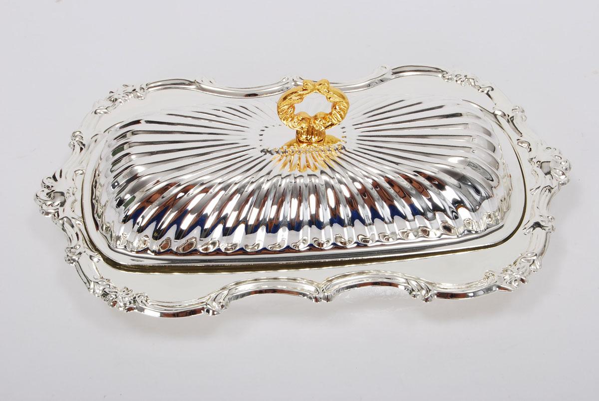 Масленка Marquis. 3034-MR3034-MRМасленка Marquis, выполненная из стали с никель-серебряным покрытием, предназначена для красивой сервировки и хранения масла. Она состоит из подноса со стеклянной емкостью и крышки с золотистой ручкой. Поднос имеет специальные выемки, благодаря которым крышка легко на него устанавливается. Масло в такой масленке долго остается свежим, а при хранении в холодильнике не впитывает посторонние запахи. Выполненная под старину, эта изысканная масленка великолепно украсит ваш праздничный стол.Размер подноса: 20 см х 12 см.Размер стеклянной емкости: 15 см х 6 см х 1,5 см.Размер крышки: 16,5 см х 8 см х 3 см.