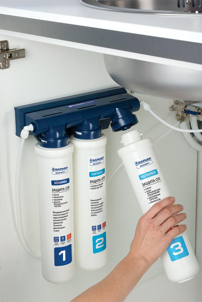 """Бытовой водоочиститель """"Барьер Expert Hard"""" - для жесткой воды. Обеспечивает эффективную очистку и   снижение жесткости воды. После фильтрации жесткость воды имеет оптимальный уровень для здоровья,   отсутствует образование накипи. Многоступенчатая система обеспечивает высокую эффективность очистки   на протяжении всего ресурса сменных фильтроэлементов, а инновационная конструкция фильтра позволяет   заменять кассету одним движением руки.  Водоочиститель """"Барьер Expert"""" удобно устанавливается под мойку. Он укомплектован всем необходимым   для самостоятельной установки. В комплект входит элегантный кран для чистой воды. """"Барьер EXPERT""""   способен работать 24 часа в сутки.    Комплект фильтроэлементов """"Барьер Expert Hard"""":   Expert Механика - предварительный фильтр. Очистка от механических загрязнений с тонкостью   фильтрации 5 мкм: песка, взвесей, ржавчины, окалины и т.д.   Expert Смягчение - уникальная технология """"byPass"""" обеспечивает оптимально снижение жесткости воды   на протяжении всего ресурса фильтроэлемента.  Expert ПостКарбон - финишная очистка. Гранулированный активированный уголь, обработанный   серебром, устраняет хлор, хлорорганические соединения, неприятные запахи, улучшает вкус воды.   Используемые технологии:   One touch - уникальная конструкция фильтра позволяет заменять картридж одним движением руки  Smartlock - самозапирающаяся система предотвращает откручивание фильтроэлементов, когда фильтр   находится под давлением   ByPass - технология позволяет максимально увеличить ресурс фильтроэлемента и избежать побочного   эффекта гиперумягчения воды.    Комплектация фильтра:  - водоочиститель в сборе с комплектом фильтроэлементов - 1 шт;  - кран для чистой воды с прокладками, шайбами, гайкой - 1 шт;  - соединительная пластиковая трубка (белая), 1 м - 2 шт;  - фитинг на кран для чистой воды - 1 шт;  - переходник-адаптер для подключения к водопроводу - 1 шт;  - шаровой вентиль для подключения к водопроводу - 1 шт;  - наклейка-шаблон для удобства подвеса фи"""