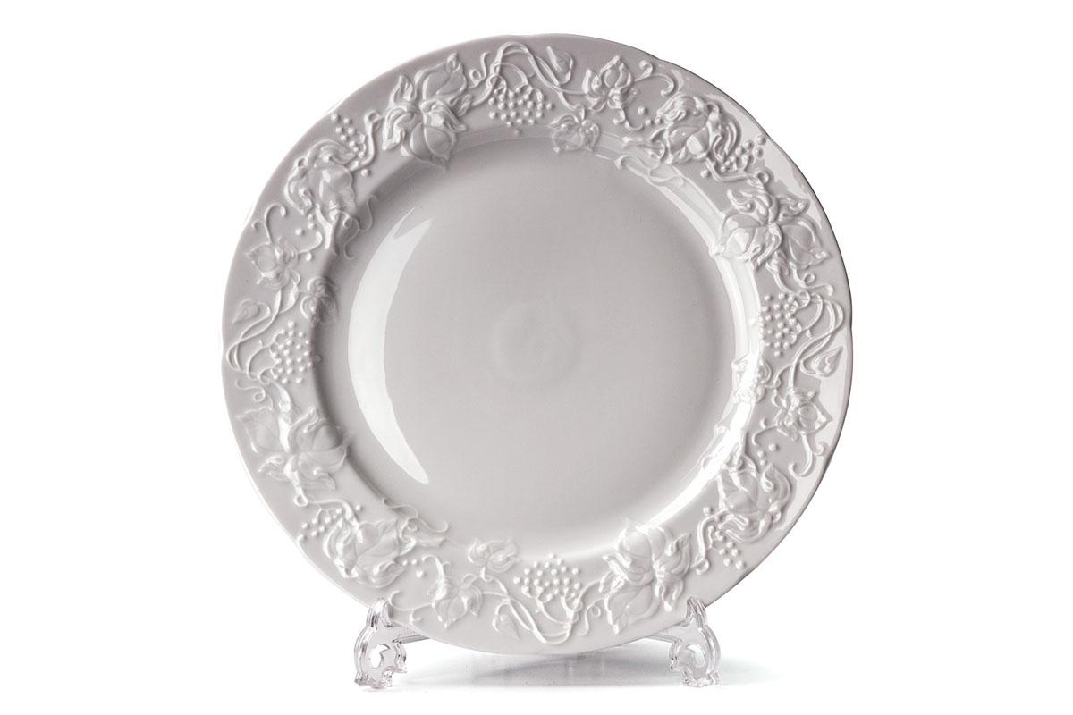Тарелка обеденная La Rose Des Sables Vendanges, цвет: белый, диаметр 26 см690126Обеденная тарелка La Rose Des Sables Vendanges - прекрасное дополнение праздничного стола. Изделие выполнено из высококачественного фарфора и украшено изысканным орнаментом. Фарфор марки La Rose Des Sables изготавливается из уникальной белой глины, которая добывается во Франции, в знаменитой провинции Лимож. Особые свойства этой глины, открытые еще в 18 веке, позволяют создать удивительно тонкую, легкую и при этом прочную посуду. Лиможский фарфор известен по всему миру. Это символ утонченности, аристократизма и знак высокого вкуса. Продукция импортируется в европейские страны и производится под брендом La Rose des Sables, что в переводе означает Роза песков. Преимущества этого фарфора заключаются в устойчивости к сколам и трещинам, что возможно благодаря двойному термическому обжигу. Посуда имеет маркировку Pate de Limoges, подтверждающую, что сырье для ее изготовления добыто именно в провинции Лимож, а качество соответствует европейским стандартам. Производство расположено в Тунисе. Коллекции бренда La Rose Des Sables самые разнообразные, от изделий в лаконичном и современном дизайне - отличный выбор на каждый день, до роскошной посуды с позолотой - для особого случая и праздничной сервировки стола. Диаметр тарелки: 26 см. Высота стенки: 2,5 см.