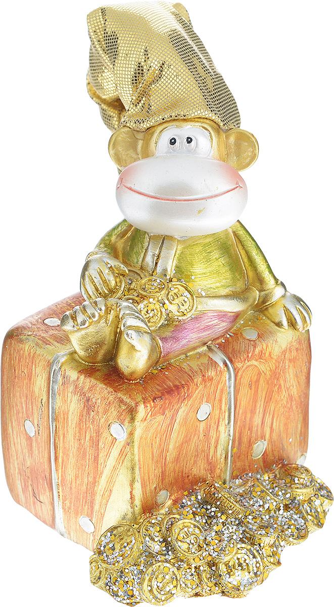 """Декоративная копилка Sima-land """"Обезьянка на подарке"""", изготовленная из  высококачественного полистоуна, выполнена в виде обезьяны в текстильном колпаке и украшена  блестками.  Изделие оснащено отверстием для монет и резиновым клапаном, через который можно достать  деньги. Яркий оригинальный дизайн сделает такую копилку прекрасным подарком. Она послужит не  только по своему прямому назначению, но и красиво дополнит интерьер комнаты."""