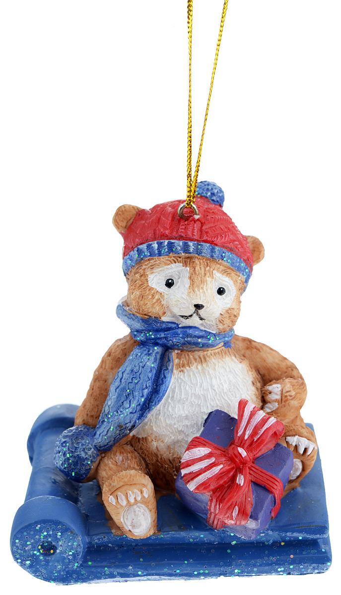 """Новогоднее украшение Феникс-Презент """"Мишка в санках"""", изготовленное из высококачественного полирезина, прекрасно подойдет для праздничного декора дома и новогодней ели. С помощью специальной текстильной петельки его можно повесить в любом понравившемся вам месте.   Елочная игрушка - символ Нового года. Она несет в себе волшебство и красоту праздника. Создайте в своем доме атмосферу веселья и радости, украшая новогоднюю елку нарядными игрушками, которые будут из года в год накапливать теплоту воспоминаний."""