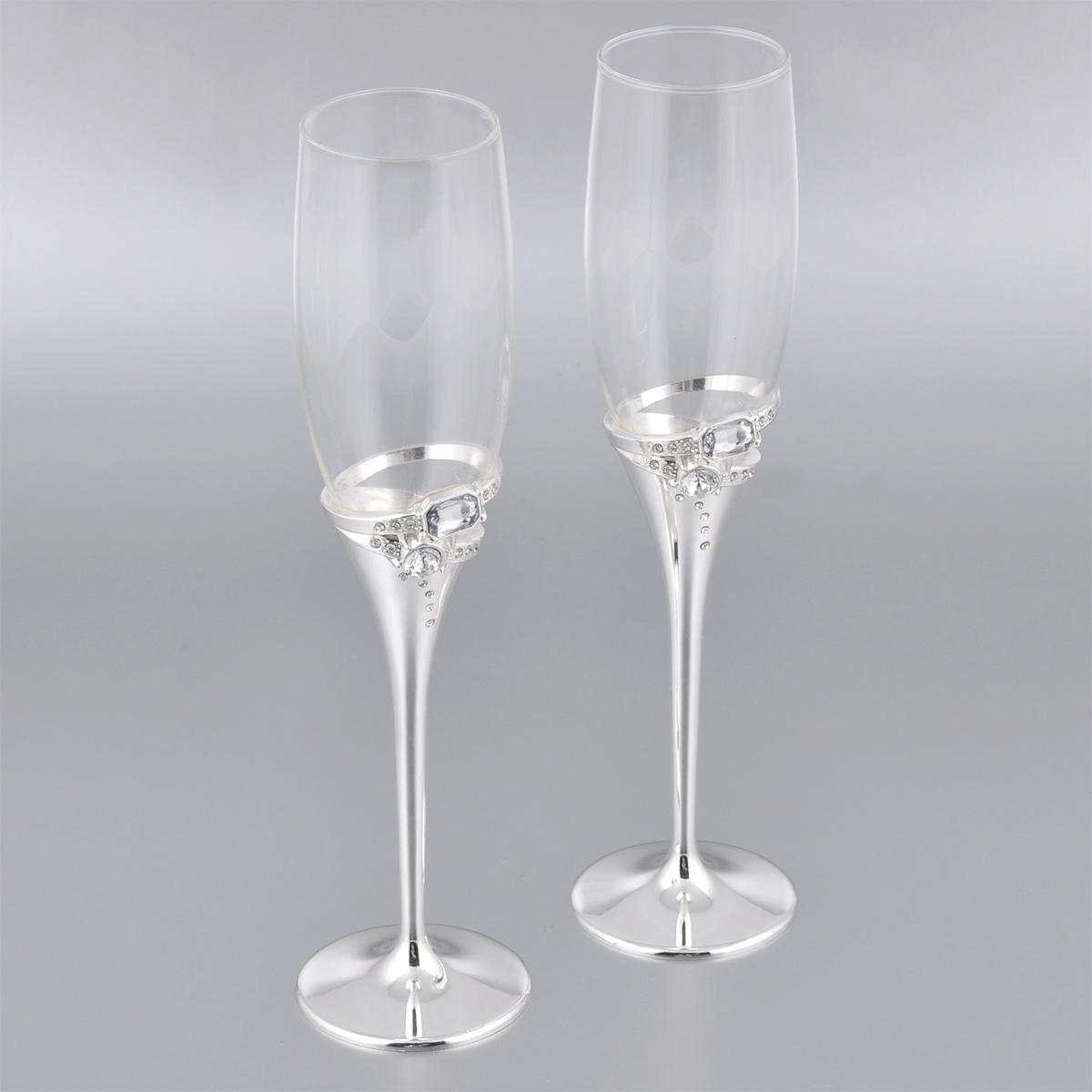 """Набор """"Marquis"""" состоит из двух бокалов на высоких ножках. Бокалы выполнены из стекла. Изящные тонкие ножки, изготовленные из стали с серебряно-никелевым покрытием, оформлены узором из страз. Бокалы идеально подойдут для шампанского или вина. Такой набор станет прекрасным дополнением романтического вечера. Изысканные изделия необычного оформления понравятся и ценителям классики, и тем, кто предпочитает утонченность и изысканность. Диаметр по верхнему краю: 5 см. Диаметр основания: 6,8 см. Высота бокалов: 25,5 см."""