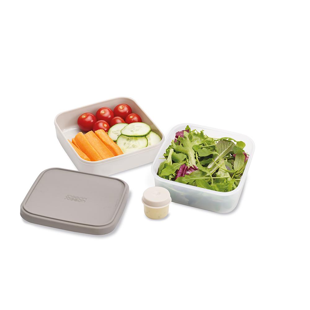 Ланч-бокс для салатов Joseph Joseph GoEat, цвет: серый. 8103081030Новая линейка универсальных контейнеров Joseph Joseph GoEat с отдельными ёмкостями для разных продуктов, специально разработана для того, чтобы вы могли брать с собой в офис или на прогулку разные блюда для полноценного обеда. Компактный контейнер для салатов Space-saving salad box идеально подходит для салатов. В верхнюю ёмкость можно положить свежие листья и зелень, в нижнюю основную - другие ингредиенты (овощи, курицу, рыбу и т.д.). Для переноски соуса есть отдельная капсула.Все контейнеры имеют герметичную силиконовую крышку и надёжное блокирующее кольцо, что гарантирует сохранность продуктов и обезопасит от протекания. Когда контейнеры пустые, они легко складываются друг в друга для удобной переноски. Верхняя ёмкость - 400 мл. Нижняя ёмкость - 700 мл.Капсула для соуса - 20 мл . Можно мыть в посудомоечной машине. Контейнеры можно разогревать в микроволновой печи, предварительно удалив кольцо и крышку.