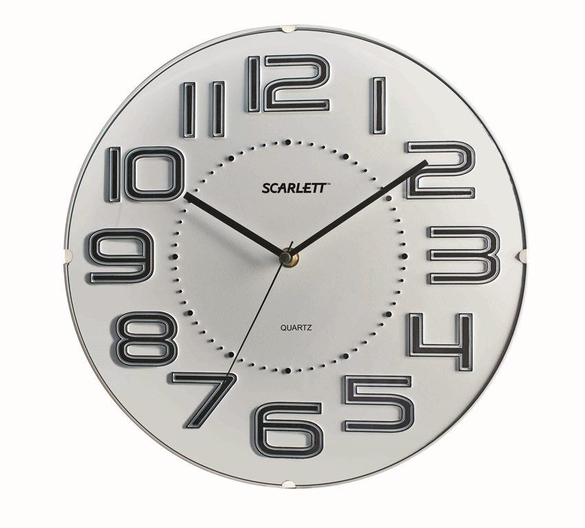 """Настенные кварцевые часы """"Scarlett"""" в классическом дизайне,  изготовленные из пластика, прекрасно впишутся в интерьер  вашего дома. Круглые часы имеют три стрелки: часовую,  минутную и секундную, циферблат защищен прозрачным  пластиком.  Часы работают от 1 батарейки типа АА напряжением 1,5 В  (батарейка в комплект не входит).   Диаметр часов: 32 см."""