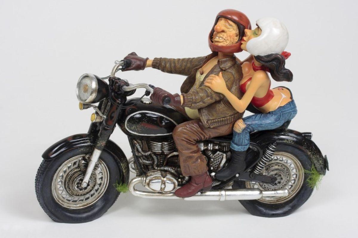 Статуэтка Gillermo Forchino Увлекательная ПоездкаFO85070Когда я встречаю приятелей в баре, они постоянно дразнят меня по поводу «маленького» пивного животика. «Кого ты собираешься соблазнять своим животом, как у бегемота?» - говорят шутники. «Ты и твой мотоцикл просто неудачники», - и они смеются, как гиены.Они даже не могли себе представить восхищение Бетти, когда я пригласил её прокатиться. «Старомодные мотоциклы возбуждают меня», - воскликнула она, усаживаясь сзади и крепко обнимая меня. – «Давай, сладенький, поехали, мне это нравится.»Я не мог в это поверить, но чувственное тело прижималось ко мне, и это было самым приятным ощущением после встречи с соседской девушкой. Я остановился перед баром, заглянул внутрь и с высокомерной улыбкой надавил на газ. Увидев лица ребят, я понял, что у них будет беспокойная ночка.