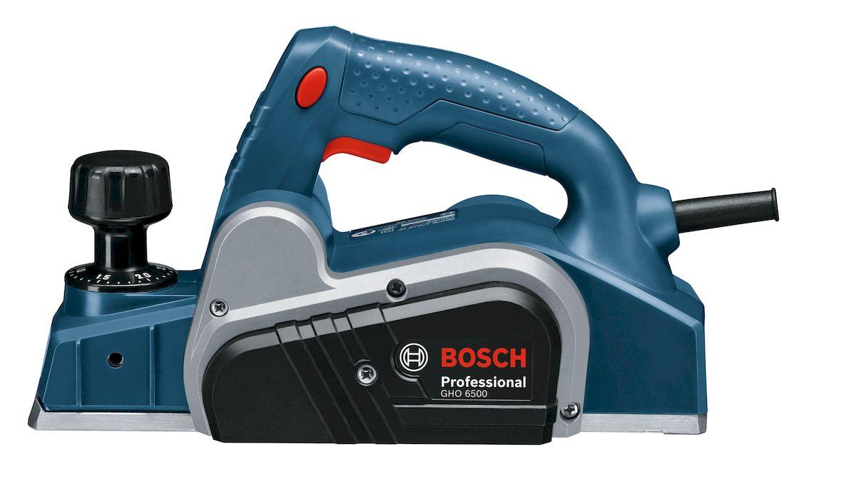 Рубанок Bosch GHO 6500. 06015960000601596000Мощный электрический рубанок Bosch GHO 6500 относится к категории ручных столярных инструментов и предназначен для проведения строительных иремонтных работ различной сложности в домашних условиях. Электрический рубанок, являясь прямым преемником обычного механического рубанка,значительно упрощает проведение работ по строганию, или обтесыванию древесных поверхностей, позволяя добиться горизонтально ровной поверхности,а так же подгонять по размеру доски и брусья путем выравнивания их профиля и уменьшения ширины в продольном сечении. Откидной пластиковый парковочный башмак позволит не повредить поверхность заготовки. Три V-образных паза разных размеров могут использоваться для точного и гибкого снятия фасок под углом.