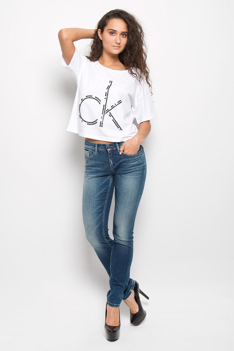 Футболка женская Calvin Klein Jeans, цвет: белый. J20J200545. Размер S (42/44)L529SWLOСтильная женская футболка Calvin Klein Jeans изготовлена из эластичного хлопка. Материал изделия мягкий, тактильно приятный, не сковывает движения и хорошо пропускает воздух, обеспечивая комфорт при носке.Укороченная модель футболки с круглым вырезом горловины и короткими рукавами имеет свободный силуэт. Изделие оформлено аппликацией в виде фирменного логотипа. Сзади на плечевом шве находится принтовая надпись, содержащая название бренда. Высокое качество, актуальный дизайн и расцветка придают изделию неповторимый стиль и индивидуальность. Футболка займет достойное место в вашем гардеробе!