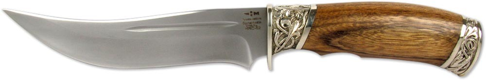 Нож Ножемир Шуйский, булатная сталь, с ножнами, общая длина 27,5 см. (5486)бШУЙСКИЙ (5486)бНож Ножемир Шуйский выполнен по восточным мотивам. Он обладает изящными и одновременно агрессивными обводами. Взлетающий кончик обладает высоким проникающим воздействием при нанесении колющего удара. Объемная рукоять обеспечивает хороший контроль при выполнении деликатных и силовых работ. Клинок выполнен из булатной стали. Рукоять ножа изготовлена из дерева зебрано, которое обладает уникальным природным рисунком. Элегантную внешность ножа дополняют литые элементы из мельхиора. Общая длина ножа: 15,2 см.Твердость стали: 62-64 HRC.