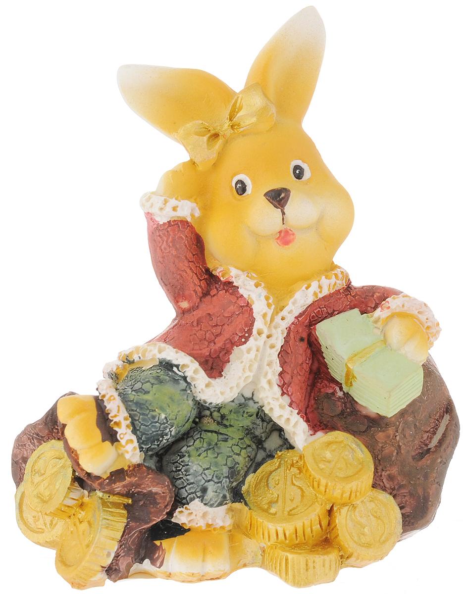 """Фигурка декоративная Феникс-Презент """"Кролик"""", выполненная из пластика, станет оригинальным подарком для всех любителей необычных вещей. Она выполнена в классическом стиле в виде кролика, лежащего на мешке с монетами. Изысканный сувенир станет прекрасным дополнением к интерьеру. Вы можете поставить фигурку в любом месте, где она будет удачно смотреться и радовать глаз."""