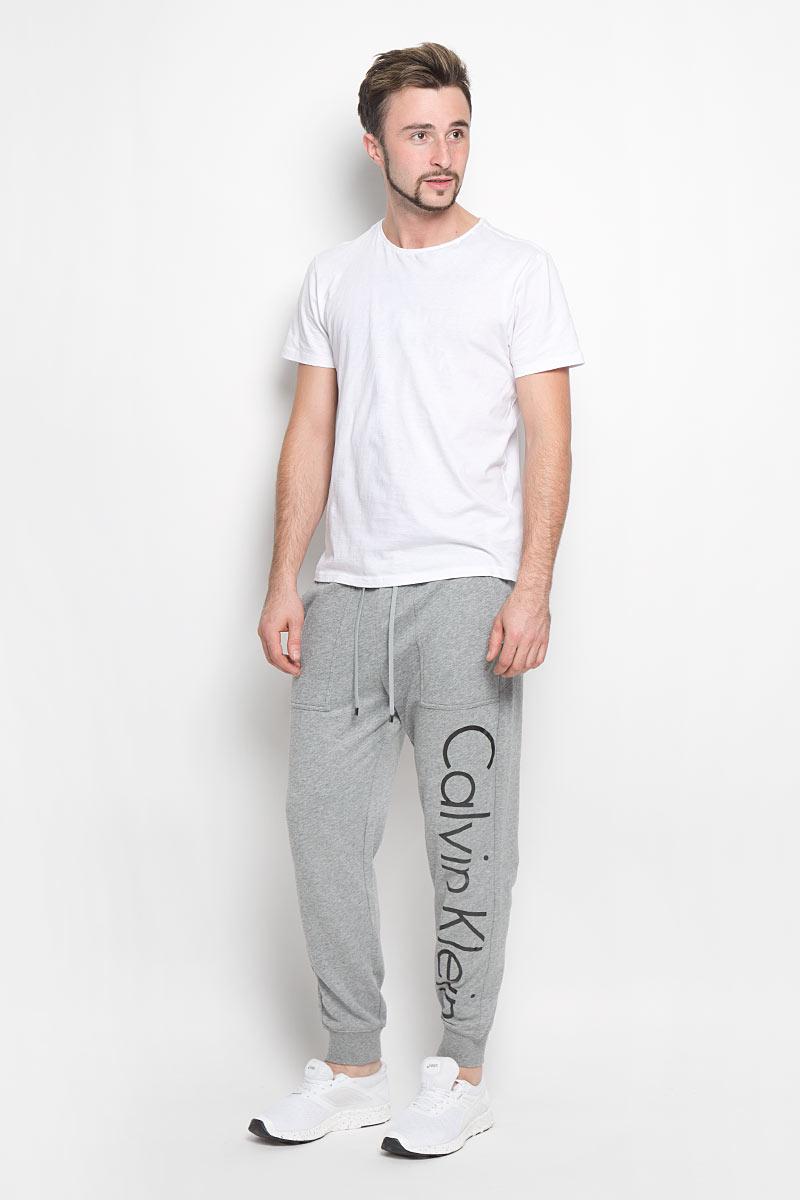 Брюки для дома мужские Calvin Klein Underwear, цвет: серый. NM1263E. Размер S (46)NM1263E_2GYМужские брюки для дома Calvin Klein Underwear выполнены из хлопка с добавлением полиэстера. Изнаночная сторона изделия с теплым начесом. Эластичный пояс с затягивающимся шнурком позволяет отрегулировать посадку точно по фигуре. Спереди расположены два втачных кармана. Низ брючин дополнен трикотажными манжетами. Оформлено изделие термоаппликацией в виде надписи.