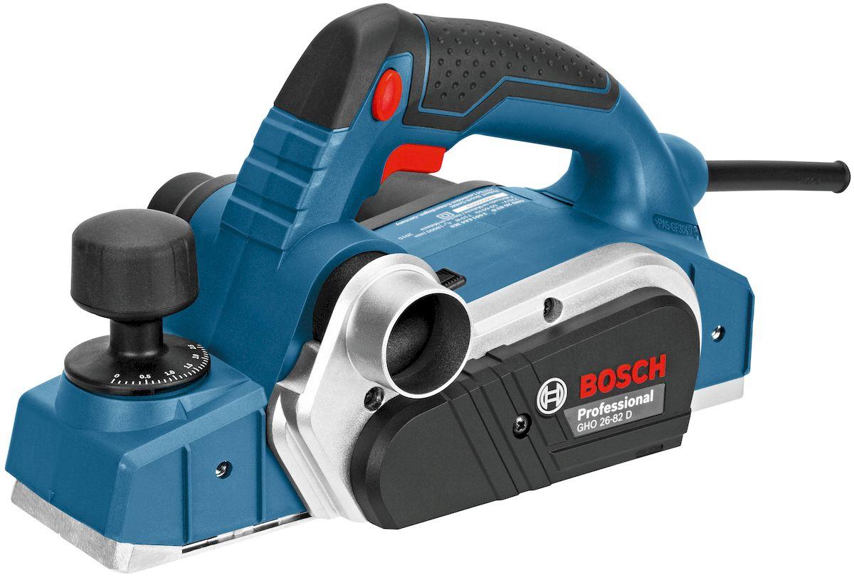 Рубанок Bosch GHO 26-82 D. 06015A430106015A4301Электрический рубанок Bosch GHO 26-82 D – это компактный отличающийся высокой производительностью инструмент, который имеет умеренную цену и хорошие привлекающие мастеров технические характеристики. Данный агрегат рассчитан на профессиональное применение. Он прекрасно справляется с работами по строганию различных пород дерева и может эффективно эксплуатироваться во многих областях деятельности. С решением соответствующих задач рассматриваемая техника справляется максимально качественно. Благодаря возможности регулировать толщину стружки и глубину выборки паза при помощи этого инструмента можно выполнять операции с высокой точностью. Ширина режущей кромки у предлагаемого устройства составляет 82 мм, а развиваемое им за минуту число оборотов имеет величину 18000. В комплект поставки этого агрегата входит мешочный фильтр из ткани, ключ с внутренним шестигранником и параллельный упор.Преимущества:- Ровная позволяющая добиваться практически идеальных результатов алюминиевая подошва.- Невысокая вибрация.- Есть возможность выбора стороны, в которую выбрасываются опилки.- Рукоятка с покрытием из резины.