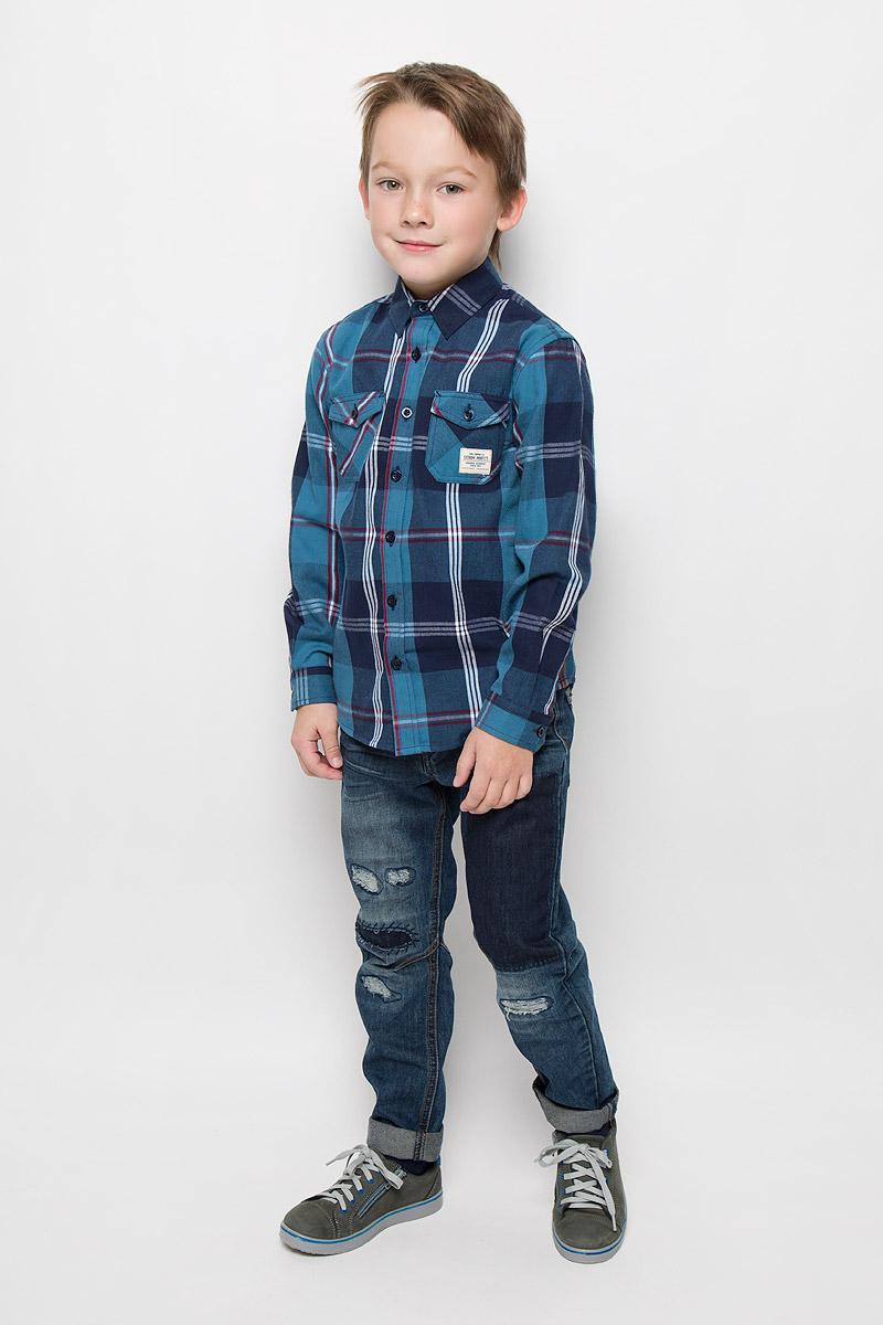 Рубашка для мальчика Sela, цвет: синий. H-812/192-6415. Размер 116, 6 летH-812/192-6415Рубашка для мальчика Sela выполнена из натурального хлопка. Рубашка с отложным воротником и длинными рукавами застегивается на пуговицы. На манжетах также предусмотрены застежки-пуговицы. На груди модель дополнена двумя накладными карманами с клапанами на пуговицах. Спинка изделия удлинена. Рубашка оформлена принтом в клетку, украшена контрастной прострочкой и фирменной нашивкой.