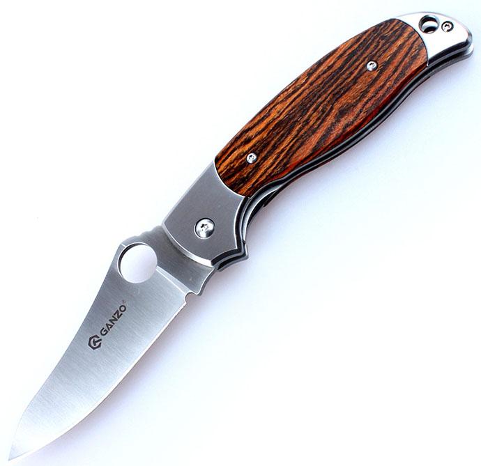 Нож туристический Ganzo, цвет: дерево, стальной, длина лезвия 8,9 см. G7371G7371-WD1Нож Ganzo относится к категории складных карманных клинков. Он выполнен из нержавеющего и долговечного вида стали. Лезвие ножа гладко заточено и отполировано методом сатинирования. Элементы рукоятки сделаны из стеклопластика.Модель выглядит внушительно и солидно. При этом, нож имеет совсем небольшие размеры, а в сложенном состоянии легко умещается в карман. Производители выбрали для него одну из наиболее сбалансированных нержавеющих сталей - 440С. При высокой стойкости к коррозии, этот металл можно закалить до твердости 58HRC. Сталь с такими показателями относительно легко затачивается, но долго не затупляется. Заточка в модели - гладкая. Размерные характеристики клинка по длине - 89 мм, по ширине обуха - 0,33 см. Клинок обработан методом сатинирования, отчего его поверхность стала блестящей, с едва заметными следами шлифовки поперек лезвия. В сторону рукояти клинок существенно расширяется и на нем есть сквозное круглое отверстие. С помощью этого отверстия, которое выполняет роль шпенька, сложенный нож можно легко открыть. В него встроен классический замок Liner с максимально простой, но непререкаемо надежной конструкцией. Он делает использование Ganzo G7371 безопасным при любых условиях.Рукоятка ножа скомбинирована из двух материалов: стали и стеклопластика. Стальные элементы - это основа, окончания рукоятки с обеих сторон, а также прижимная клипса. Все они тщательно отполированы, что добавляет ножу презентабельности. Центральная часть с обеих сторон представлена накладками из G10. Эта разновидность пластика прочнее других, а потому хорошо себя зарекомендовала в производстве ножей. Поверхность ручки - текстурная, чтобы его можно было крепче держать, окрашена в черный или же оранжевый цвет.Длина лезвия: 8,9 см.Ширина обуха: 3,3 мм.Длина рукоятки: 12,1 см.Вес: 164 г.