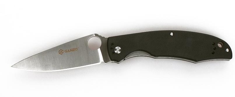 Нож туристический Ganzo, цвет: черный, стальной, длина лезвия 9,5 см. G732G732-BKУдобный и практичный складной нож Ganzo подойдет для использования на рыбалке или охоте, а также в любых туристических походах и путешествиях. Его клинок сделан из качественной марки стали, а рукоятка ножа - из стеклопластика G10.Складной нож с первого взгляда привлекает внимание дизайном. У него широкий клинок необычной формы с отверстием круглой формы, которое выполняет роль шпенька для открывания. Рукоятка подогнана под форму руки. Но внимания заслуживает не только дизайн ножа, но и материалы, из которых он изготовлен.Для клинка производители выбрали хорошо известную марку стали - 440С. Это нержавеющий сплав высокого качества, который широко используется для производства ножей среднего ценового сегмента. Эта сталь позволяет произвести закалку до твердости около 58 единиц в соответствии со шкалою Роквелла. Длина клинка ножа равна 9,5 см при толщине его обуха 0,33 см. Поверхность клинка отшлифованная. Режущая кромка получила классическую ровную заточку, которая используется в работе практически с любыми материалами.Основа рукоятки ножа также металлическая, но на металле закреплены накладки из G10. Это современный вид композитного пластика, состоящего из стекловолокна и эпоксидной смолы. Ему легко придать необходимую форму и окрасить накладки в выбранный цвет. В хвосте рукоятки есть небольшое отверстие для присоединения темляка. А ближе к клинку прикручена металлическая клипса для поясного ремня, которая держится на трех болтах.В готовом к выполнению работ виде, нож имеет длину 215 мм. В сложенном же он легко помещается в карман. Чтобы клинок не мог случайно открыться, он фиксируется механизмом Liner-Lock. Ножевой замок такой конструкции очень простой, но эффективный и целиком исключает возможность случайного срабатывания.Общая длина ножа: 21,5 см.Длина лезвия: 9,5 см.Толщина клинка: 3,3 мм.Вес ножа: 125 г.
