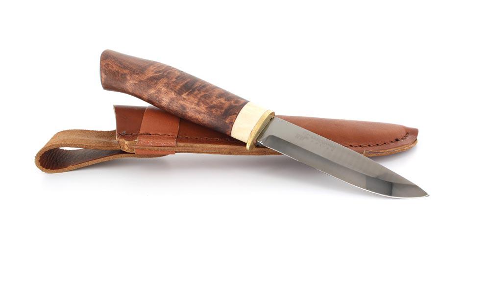 Нож Karesuando Marten Graphit-IC, цвет: коричневый, длина клинка 9,8 см. KR/3582KR/3582Мастера компании изготавливают клинки ножей «Каресуандо» из нержавеющей стали, высокоуглеродистой стали, современной порошковой стали и высококачественного дамаска. Рукояти ножей изготавливаются из местной карельской березы. Многие модели имеют дополнительные элементы в виде вставок из рога северного оленя и бронзы (больстер, гарда, навершие). Все изделия комплектуются качественными ножнами из натуральной кожи.Скандинавские ножи от Karesuando — это яркий пример качественных режущих инструментов, готовых к самым жестким работам. Режущие кромки ножей с клинками из нержавеющей стали имеют твердость не ниже 57 единиц по шкале Роквелла. Такие клинки остаются острыми длительное время, даже при весьма жестком применении. Режущие кромки лезвий из углеродистой стали, порошковой стали и дамаска имеют более высокую твердость.Ножи с клинками из порошковой стали и дамаска используются в линейках ножей класса премиум. Предприятие предлагает своим клиентам не только добротные и функциональные режущие инструменты, но и изысканные ножи, достойные места в коллекции ножемана.Предприятие Karesuando для ножей премиум сегмента использует клинки из многослойной стали Damasteel, одной из лучших дамасских сталей в мире. Для клинков ножей используется нержавеющий дамаск в 120–160 слоев.Общая длина ножа: 21,2 см.Длина клинка: 9,8 см.Толщина клинка: 3 мм.Длина рукояти: 11,4 см.Толщина рукояти: 1,8 см.
