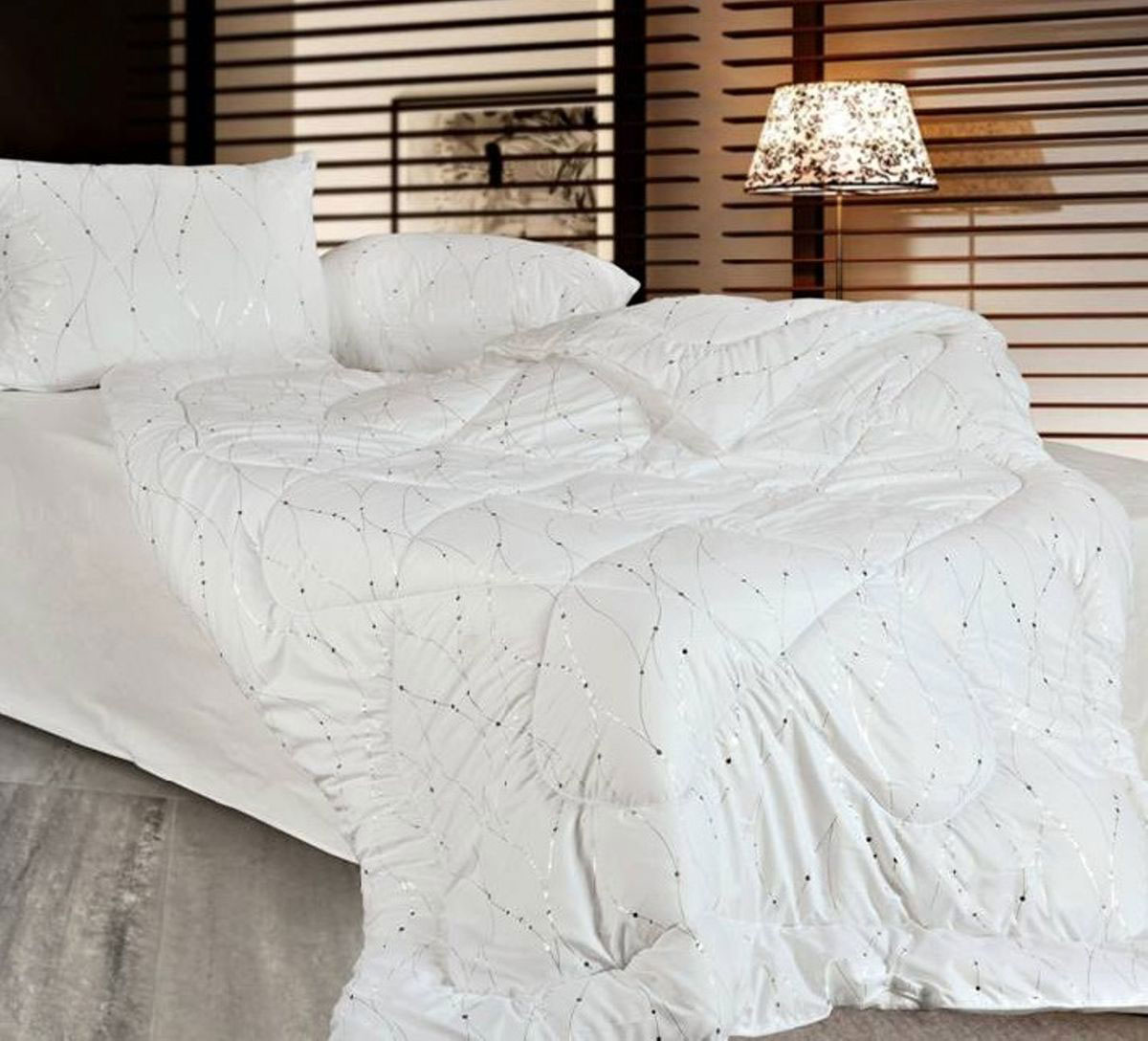 """Классическое одеяло с экологичным наполнителем и стильным верхом - серебро  на белом фоне - простегано - значит, наполнитель внутри будет всегда  распределен равномерно.  Чехол одеяла """"Home & Style"""" выполнен из микрофибры.  Наполнитель - соевое волокно.  Размер: 172 х 205 см."""