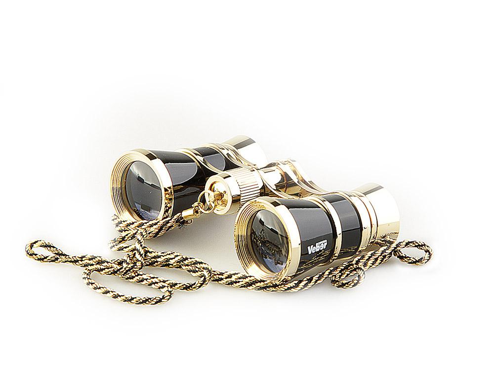 Бинокль Veber Opera, с цепочкой, цвет: черный, БГЦ 3x25 D0210996Светосильный, корпус — металл, оптическое стекло с просветлением. Отделка глянцевым черным лаком и напыленным 18-ти каратным золотом. Регулируемое межзрачковое расстояние, фокусировка, металлическая цепочка. ОПИСАНИЕТеатральный бинокль Veber Opera БГЦ 3x25 - не только изящный аксессуар, но и незаменимый помощник в наблюдениях театральных, цирковых, эстрадных представлений, верный спутник на экскурсиях. Классическая галилеевская оптическая схема с центральной внутренней фокусировкой, заключенная в черный лакированный корпус с позолоченными (18к) элементами. Трехкратное увеличение и широкое поле зрения позволят вам насладиться представлением даже с галерки. Особенности Галилеевская оптическая система Центральная внутренняя фокусировка 3-х кратное увеличение Комплектация Бинокль Футляр-мешочек Ткань для протирки оптики Металлическая цепочка 100 см Руководство по эксплуатации и гарантийный талон Характеристики Увеличение, крат 3 Диаметр объектива, мм 25Вес, г 190 Цвет черный/золотой