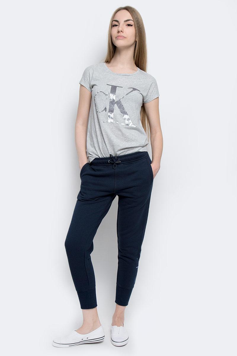 Брюки спортивные женские Calvin Klein Jeans, цвет: темно-синий. J20J201232_4720. Размер L (48/50)J20J201232_4720Женские спортивные брюки Calvin Klein Jeans, изготовленные из хлопка с добавлением полиэстера, идеально подходят как для активного отдыха, так и для неспешных прогулок. Модель выполнена на эластичном поясе, который дополнен с внутренней стороны эластичной резинкой с названием бренда. Обхват талии регулируется с помощью затягивающегося шнурка. Спереди модель дополнена двумя втачными карманами, а сзади двумя прорезными. Низ брючин выполнен на трикотажной резинке. Оформлены брюки принтом с вышитым названием бренда.