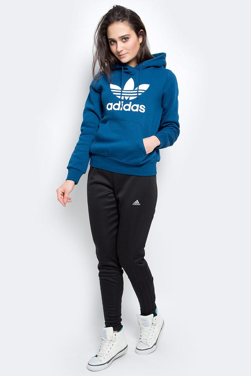 Толстовка женская adidas Trf logo hoodie, цвет: синий. AY8112. Размер 32 (38)AY8112Проверенный временем спортивный стиль покоряет современные улицы городов. Карманы-кенгуру со вставкой из гладкого, приятного на ощупь нейлона. Приталенный крой. Стильные светоотражающие детали. Капюшон из трех частей на регулируемых завязках-шнурках.