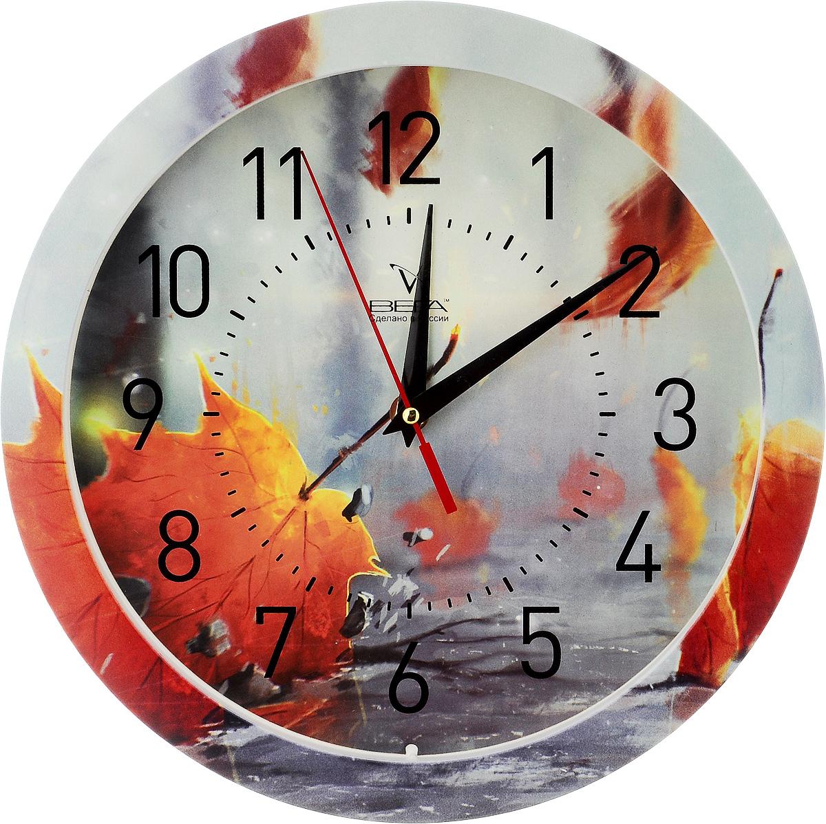 Часы настенные Вега Осень, диаметр 28,5 смП1-240/7-240Настенные кварцевые часы Вега Осень, изготовленные изпластика, прекрасно впишутся в интерьер вашего дома. Часыимеют три стрелки: часовую, минутную и секундную, циферблатзащищен прозрачным стеклом.Часы работают от 1 батарейки типа АА напряжением 1,5 В (невходит в комплект). Диаметр часов: 28,5 см.